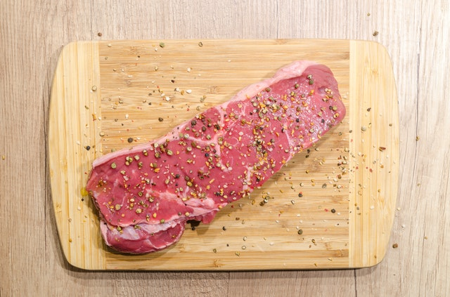 Raw seasoned beef on cutting board.